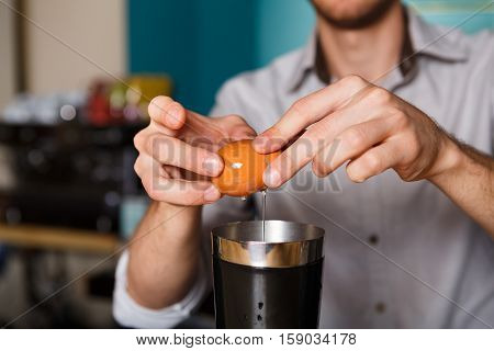 Barman's hands in bar interior making alcohol cocktail. Professional bartender at work in bar pouring egg yolk into glass for drink. Party time in night club