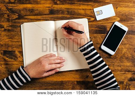 Woman writing contact list from mobile phone into her business agenda notebook for backup top view of office desktop