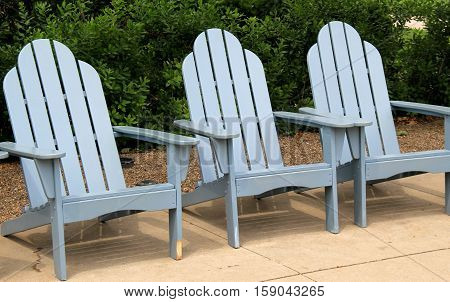 Trio of gray Adirondack chairs on stone patio, with hedges behind.