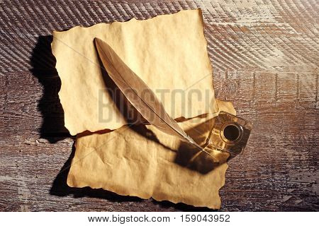 Feather pen with inkwell and papers on wooden table closeup