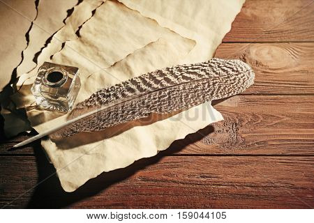 Feather pen with inkwell and blank papers on wooden table closeup