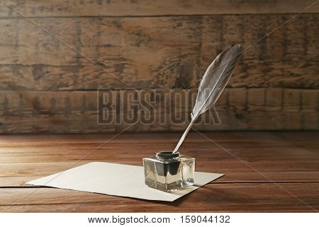 Feather pen with inkwell and blank paper on wooden background