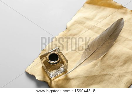Feather pen with inkwell and blank paper on light background