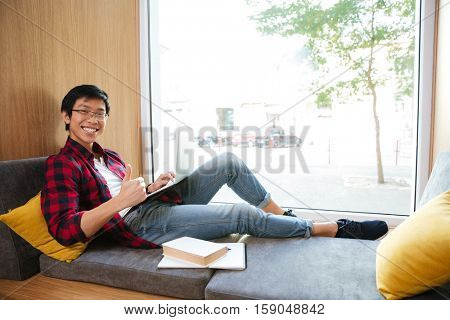 Image of happy asian student using laptop in university library sitting on sofa near book and notebook.