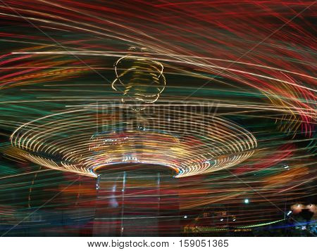 Moving carnival ride at night with swirly lights