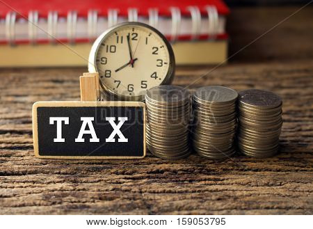 coins and time with wooden tag and text of tax concept time for tax or business.