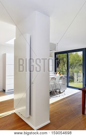 Vertical Radiator On A Column In A Spacious Apartment