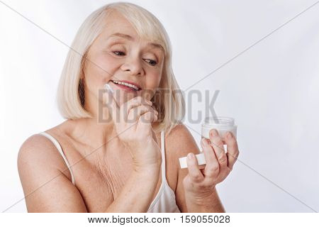 Fight with age. Joyful nice good looking woman holding a cream bottle and holding a finger while intending to put anti age cream on her face