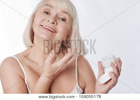 Facial cosmetics. Optimistic joyful senior woman putting cream on her face and smiling while enjoying the beauty procedure
