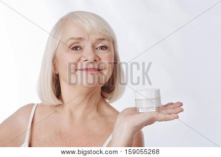Beauty products. Positive smiling aged woman having a cream bottle on her palm and smiling while presenting beauty products