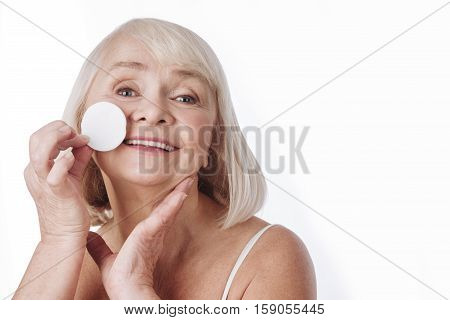 Natural beauty. Good looking happy elderly woman using a cotton pad and removing her make up while cleaning her skin