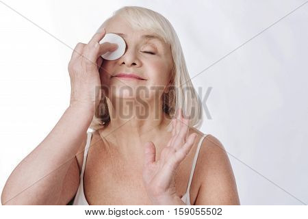 Removing make up. Nice positive aged woman cleaning her skin and smiling while using a cotton pad