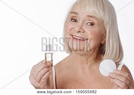 Cosmetic products. Elated happy elderly woman holding a cleansing lotion and a cotton pad and smiling while using cosmetic products