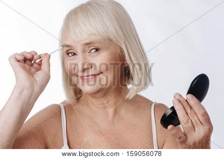 Cotton buds. Nice optimistic elderly woman holding a cotton bud and using it while having a mirror in her hand