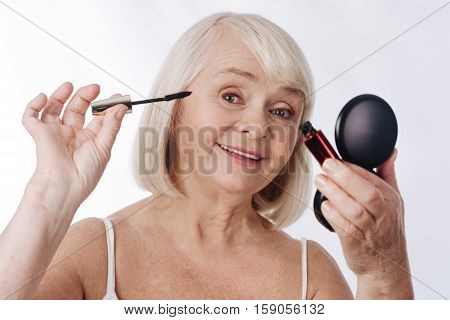 Beautiful eyelashes. Pleasant happy aged woman holding mascara and using in while putting on make up
