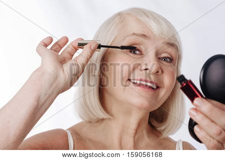 Beautiful look. Nice cheerful elderly woman holding a mascara brush and smiling while applying make up