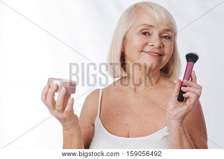 Cosmetic tools. Happy positive senior woman holding a cosmetic brush and face powder and smiling while looking at you