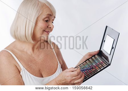 Wide choice of colour. Good looking cheerful senior woman holding a makeup brush and choosing the color while applying eyeshadow