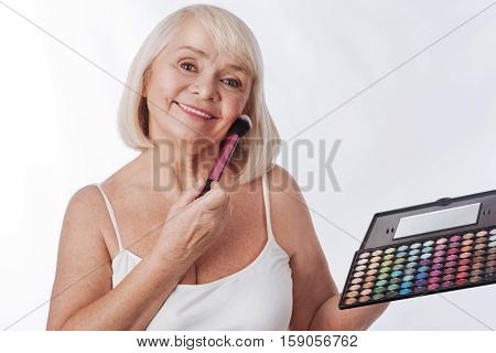 Professional make up. Joyful grey haired retired woman holding an eyeshadow palette and using a cosmetic brush while putting on professional make up