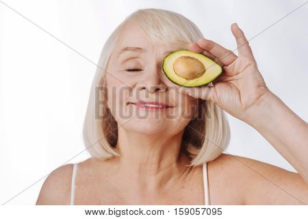 Fresh fruits. Charming relaxed pleasant woman holding an avocado half near her eye and smiling while closing her eyes