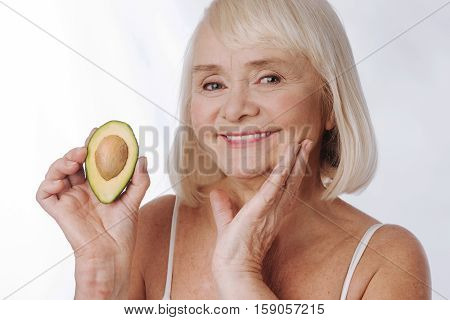 I love avocados. Happy charming retired woman standing against white background and holding an avocado half while touching her chin