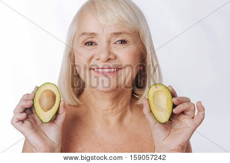 Fruits in cosmetic industry. Pleasant charming senior woman holding two avocado halves and smiling while showing them to you
