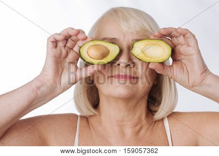Avocado facial mask. Delighted grey haired elderly woman standing against the white background and holding avocado halves while putting them to her eyes