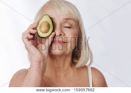 Natural beauty. Delighted relaxed grey haired woman closing her eyes and holding an avocado half near her eye while enjoying her relaxation