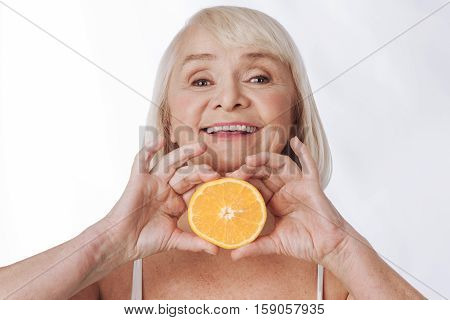 I like citrus fruits. Nice content elderly woman holding a half of an orange and smiling while feeling great