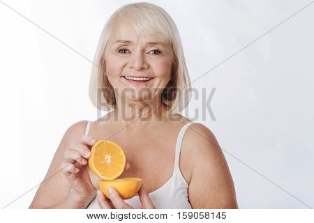 Citrus fruits in cosmetics. Cheerful charming senior woman holding halves of an orange and smiling while using them in cosmetics