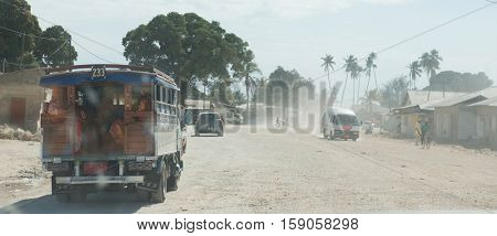 dusty road with transport and walking people leading to Zanzibar town on July 14, 2016 in Zanzibar