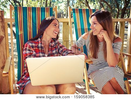 Mid shot of two pretty young women sitting together and chattering on a good sunny day. Toothy smiling when discussing some news during the leisure time
