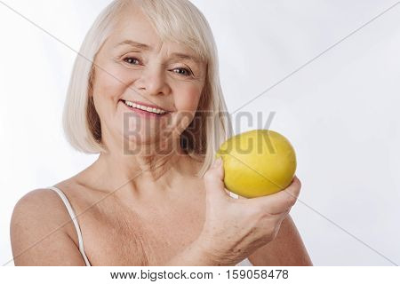 Tasty fruit. Elated good looking senior woman having a big yellow apple in her hand and intending to eat it while looking at you
