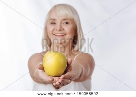 Full of vitamins. Selective focus of a big yellow apple being in hands of a positive charming smiling woman while being offered to you