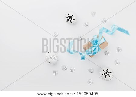 Christmas gift box with blue ribbon and jingle bell on white desk from above. Holiday greeting card. Mockup. Flat lay composition.