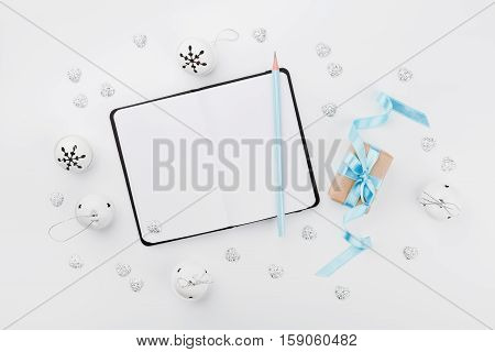 Christmas gift box with blue ribbon empty notebook and jingle bell on white table from above. Holiday greeting card. Mockup. Flat lay composition.