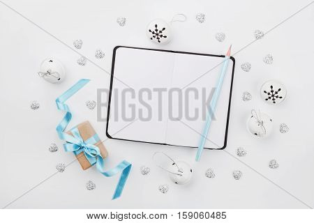 Christmas gift box with blue ribbon empty notebook and jingle bell on white desk from above. Holiday greeting card. Mockup. Flat lay composition.