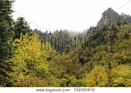Stark granite peaks above bright foliage near Dixville Notch in New Hampshire