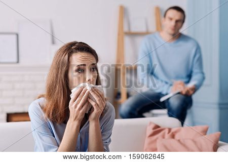 Every day troubles. Distressed woman sitting on the couch and feeling depressed while consulting with spychologist