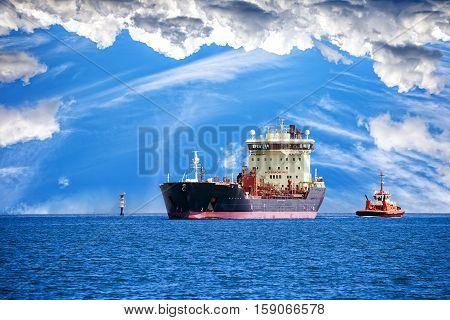 Tug boat towing a tanker ship at sea.
