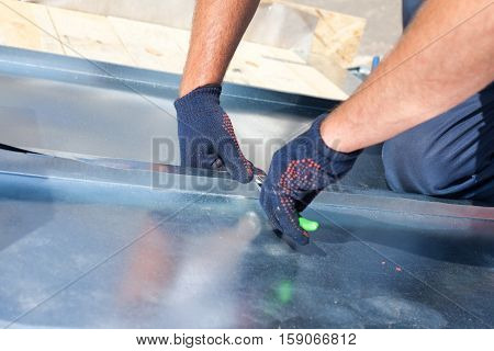 Roofer builder worker finishing folding a metal sheet using special pliers with a large flat grip