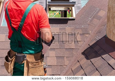 Roofer builder worker with bag of tools installing roofing shingles