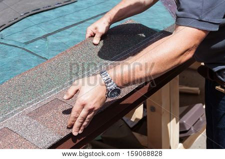 Roofer builder worker installing roof shingles closeup