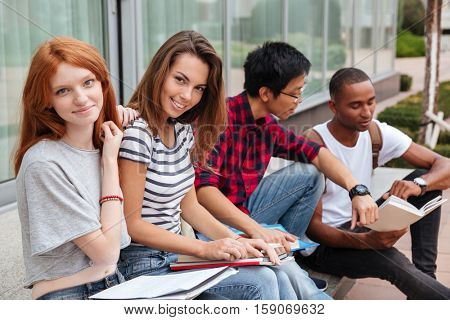 Multiethnic group of happy young students sitting and talking outdoors