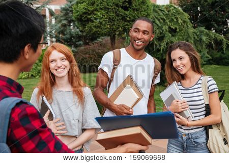 Multiethnic group of smiling young students standing and talking outdoors
