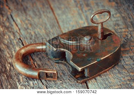 Old padlock with the key in the keyhole lying on a wooden board