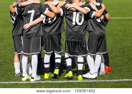Young football soccer players in black sportswear. Young sports team with football coach. Pep talk with coach before the final match. Soccer school tournament