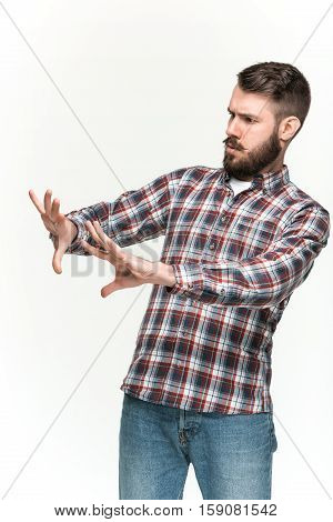 Man wearing a checkered shirt is looking scared t an imaginary object in his hands. Over white background