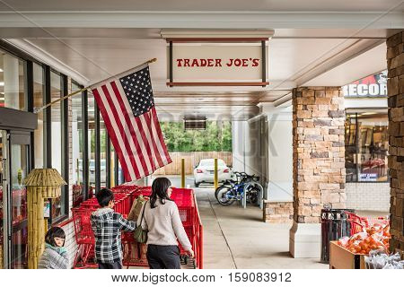 Fairfax, USA - November 25, 2016: Trader Joes grocery store entrance with sign, American flag and people walking