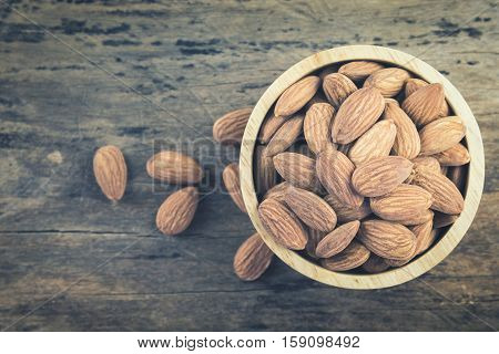 Almonds in brown bowl on textured wooden background top view. Copy space on left side. Almond vintage tone